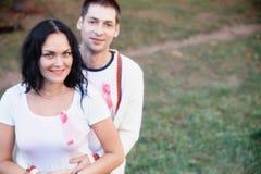 Donna ed uomo con il nastro rosa per la guarigione il giorno del cancro del mondo immagine stock