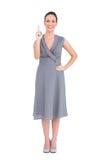 Donna elegante allegra in vestito di classe che indica il suo dito su immagini stock