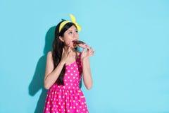 Donna elegante attraente che mangia lo spuntino della ciambella immagine stock libera da diritti