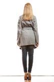 Donna elegante bionda nella retrovisione del cappotto grigio immagini stock libere da diritti