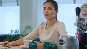 Donna elegante che chiede una fattura mentre sedendosi al contatore del caffè Fotografia Stock Libera da Diritti