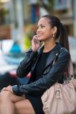 Donna elegante che comunica sul telefono astuto immagine stock