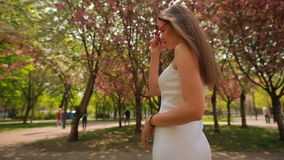 Donna elegante che indossa i vetri rosa che stanno agli alberi del fiore nel parco di estate video d archivio