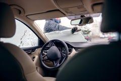 Donna elegante che libera il parabrezza dell'automobile dalla neve Immagini Stock Libere da Diritti