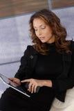 Donna elegante che per mezzo del calcolatore del ridurre in pani immagini stock