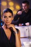 Donna elegante che si siede alla tabella di pranzo Fotografia Stock