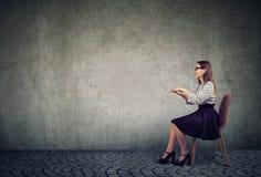 Donna elegante che si siede alla tavola invisibile che finge di scrivere sul computer immagine stock libera da diritti