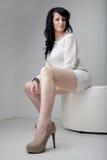 Donna elegante che si siede in sofà rotondo bianco Immagini Stock Libere da Diritti