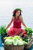 Donna elegante con le verdure in una barca Fotografia Stock