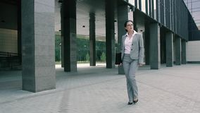 Donna elegante di affari che tiene un caso del documento archivi video