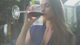 Donna elegante graziosa con capelli lunghi che beve vino rosso dall'alto vetro nella luce morbida La signora si rilassa, lei ? video d archivio
