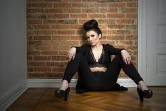Donna elegante lunatica che si siede su un pavimento di parquet immagini stock libere da diritti