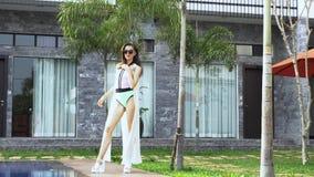 Donna elegante nella posa all'aperto della villa di lusso vicino alla piscina Femmina in costume da bagno colourful, capo bianco  video d archivio