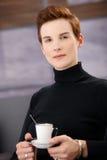 Donna elegante sorridente che mangia caffè Immagini Stock