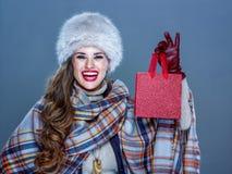 Donna elegante sorridente che mostra piccolo sacchetto della spesa rosso immagine stock libera da diritti