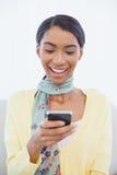 Donna elegante sorridente che si siede sull'invio di messaggi di testo del sofà Immagini Stock