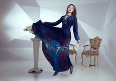 Donna elegante in un vestito lungo che salta sul fondo del modello triangolare geometrico bianco e dell'interno minimalistic Immagine Stock