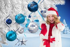 Donna emozionante in cappello di Santa che mostra il suo regalo contro il fondo digitalmente generato di natale immagini stock libere da diritti