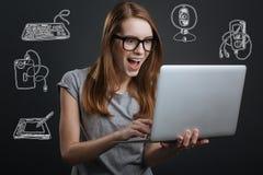 Donna emozionante che apre la sua bocca mentre esaminando la vendita in Internet immagini stock