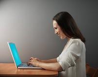 Donna emozionante che lavora con il computer portatile Immagine Stock