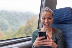 Donna emozionante che tiene uno smartphone e che vince sulla linea sul viaggio in treno immagini stock