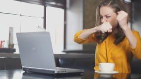 Donna emozionante che utilizza computer portatile nel caffè, lotteria online di conquista, ballo della vittoria stock footage