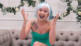 Donna emozionante che vi esamina che vi sedete su un sofà nel salone a casa fotografia stock