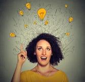 Donna emozionante con cercare capo di cui sopra di molte lampadine di idee Immagini Stock