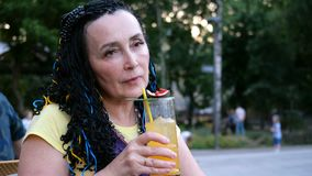 Donna esagerata senior che beve un cocktail di frutto della passione che si siede in un caffè della via nel parco fra gli alberi video d archivio