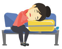 Donna esaurita che dorme sulla valigia all'aeroporto Fotografia Stock