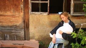 Donna esaurita, madre con un infante nelle sue armi sui precedenti delle case bombardate Guerra, terremoto, fuoco archivi video