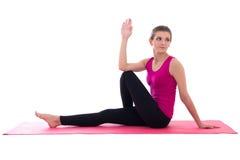 Donna esile attraente che fa allungando esercizio sull'isolante della stuoia di yoga Immagine Stock