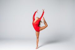 Donna esile bionda di giovane bellezza nell'ente rosso che salta e che fa gli esercizi relativi alla ginnastica su fondo bianco fotografia stock
