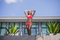 Donna esile che allunga yoga nella vista del mare di mattina della piscina Fotografia Stock