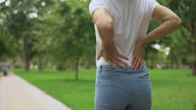 Donna esile che cammina nel parco, disagio ritenente di dolore posteriore, reumatismo, sanità archivi video