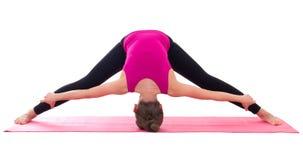Donna esile che fa allungando esercizio sulla stuoia di yoga isolata sul whi Fotografia Stock