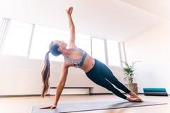 Donna esile che fa la posa di yoga della sponda Immagini Stock