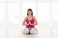 Donna esile che medita nella palestra che si siede sulla stuoia di yoga fotografia stock libera da diritti