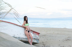 Donna esile in costume da bagno che si appoggia una barca di legno immagine stock