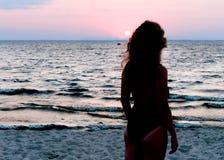 Donna esile in costume da bagno che sta e che esamina alba vicino al mare sulla spiaggia fotografia stock libera da diritti