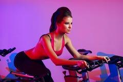 Donna esile sulla bicicletta di esercizio nel club di forma fisica Fotografie Stock