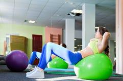 Donna esile sulla palla di forma fisica Fotografia Stock