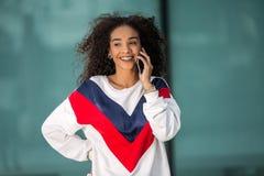 Donna etnica alla moda che parla sul telefono immagini stock