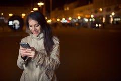 Donna euforica che per mezzo del suo Smart Phone e sorridendo al messaggio di buone notizie Messaggio di testo di battitura a mac Fotografie Stock Libere da Diritti