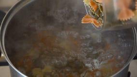 Donna europea che cucina il farfalle della pasta dell'arco video d archivio