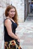 Donna europea che pende alla parete di pietra, stando indietro, esaminante macchina fotografica Copyspace immagini stock
