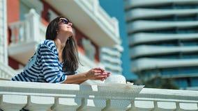 Donna europea elegante in occhiali da sole che stanno sul terrazzo che si appoggia inferriata antica che gode del sole archivi video
