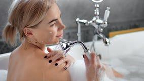 Donna europea nuda sorridente seducente del primo piano giovane che prende doccia che si rilassa nel bagno video d archivio
