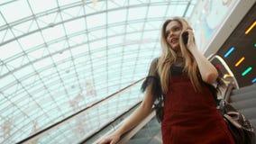 Donna facendo uso dello smartphone nella fine del centro commerciale sul video di riserva del colpo 4K archivi video