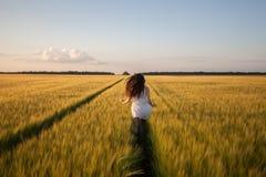Donna fatta funzionare nel giacimento di grano giallo Fotografia Stock Libera da Diritti